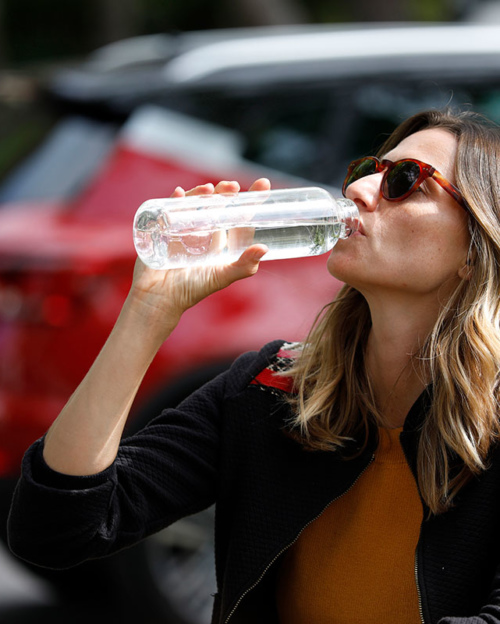 Woman drinking from a reusable bottle