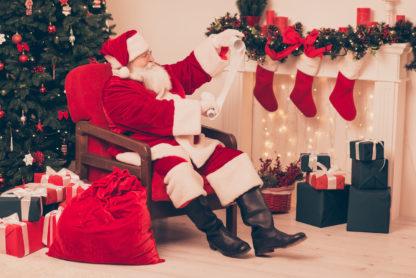 Santa reading a list of six cars for Santas stocking